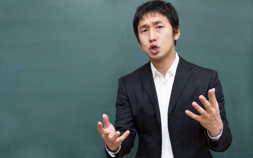 黒板の前に立つ教師
